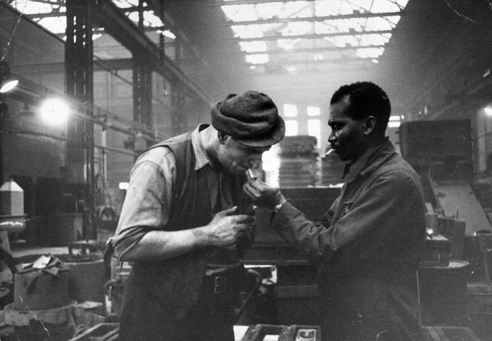 Jamaican immigrant Kwessi Blankson gives a light to workmate Jack White in 1955